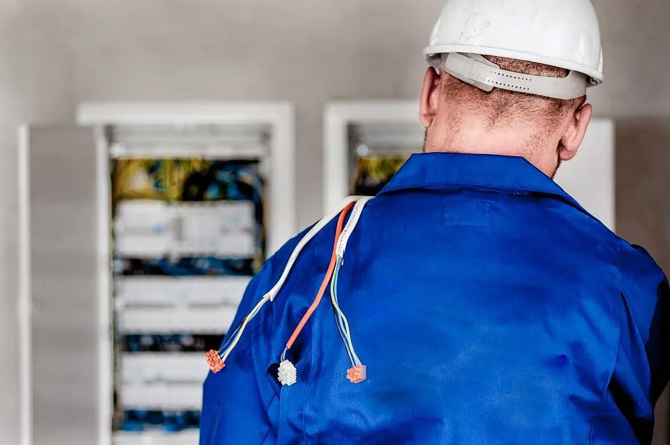 Male electricians consults an electrical panel